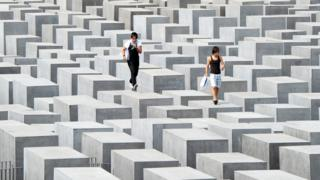 This file photo taken on 6 August, 2010 shows two tourists jumping over the concrete steles of the Holocaust Memorial in Berlin.