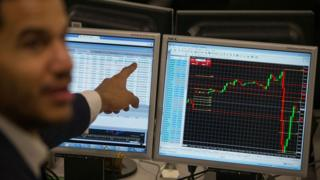 A trader points to a the trading terminal screen showing the S&P 500 Index, as he works at ETX Capital in central London on November 9, 2016, following the result of the US presidential election