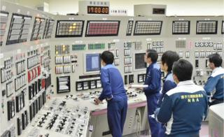 Employees of the Takahama nuclear power plant monitor instruments at its operation room
