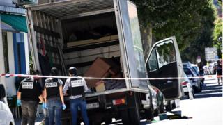 French police officers search a truck in a street of Nice on 15 July 2016, near the building where the man who drove a truck into a crowd watching a fireworks display the day before reportedly lived.