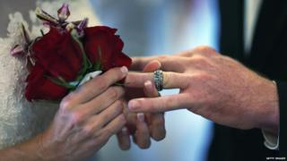 """Luanne Round slips a ring on the finger of her husband Matthew Round as they are wed during a group Valentine""""s day wedding at the National Croquet Center on February 14, 2013 in West Palm Beach, Florida."""