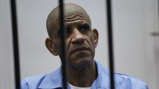 Former spy chief Abdullah al-Senussi dressed in prison blue behind the bars of the accused cell during their trial at court of appeals in the Libyan capital, Tripoli