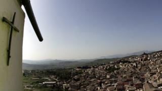 A crucifix towers over Corleone, Italy, the ancestral home and surname of the title characters in The Godfather novel and films