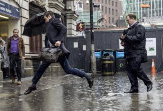 People attempting to avoid a large puddle outside Victoria Station in London