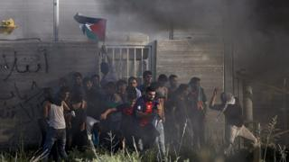 Palestinians throw stones at Israeli troops across the Gaza border fence. 9 October 2015