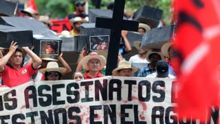 Members of the Peasant Unified Movement (MUCA) of Bajo Aguan, carry mock coffins bearing pictures of mates murdered in land conflict clashes, during a march commemorating the country's 191st independence anniversary, in Tegucigalpa, on September 15, 2012.