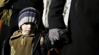 A Syrian boy waits with his family in Madaya