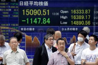 Pedestrians stand in front of a monitor displaying the Tokyo stock index