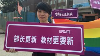 Qiu Bai holds up a sign