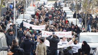 """People hold a sign reading """"Justice for Theo"""" during a protest on 6 February 2017 in Aulnay-sous-Bois, northern Paris, a day after a French police officer was charged with the rape of a youth who was severely injured after allegedly being sodomised with a baton"""