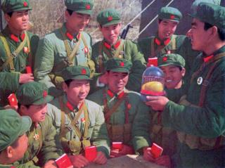 Members of the People's Liberation Army look at a wax replica mango in a glass case