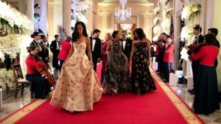 The Obama family, including the first lady Michelle and her two daughters, walk down a red-carpeted hallway flanked by musicians at a black tie reception in the White House.