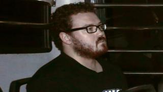 Rurik George Caton Jutting, a British banker charged with two counts of murder after police found the bodies of two women in his apartment, sits in the back row of a prison bus as he arrives at the Eastern Law Courts in Hong Kong November 24, 2014