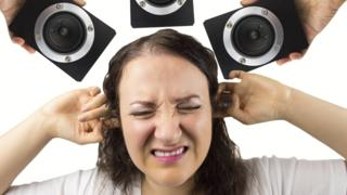 Woman holding her fingers in her ears, surrounded by speakers