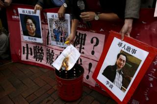 A pro-democracy demonstrator burns a letter next to pictures of missing staff members of a publishing house and a bookstore, including Gui Minhai, a China-born Swedish national who is the owner of Mighty Current, Cheung Jiping, the business manager of the publishing house and Causeway Bay Books shareholder Lee Bo (L-R), during a protest to call for an investigation behind their disappearance, outside the Chinese liaison office in Hong Kong, China 3 January 2016