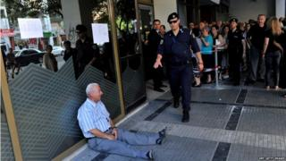 An elderly man is crying outside a national bank branch as pensioners queue to get their pensions, with a limit of 120 euros, in Thessaloniki on 3 July, 2015.