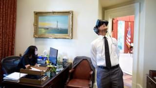 Just outside the Oval Office, Barack Obama looks to the ceiling, wearing a virtual reality headset over his eyes and ears, as a staff member ignores him and works on her computer.