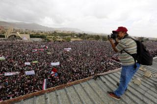 A Yemeni photographer takes photos of a rally in Sanaa