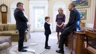 Obama, leaning casually against his desk, looks at six-year-old Alex, dressed in a suit, in a visit to the Oval Office. Alex's mother looks on as his father holds a smaller girl in his arms.