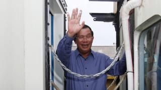 Cambodia's Prime Minister Hun Sen greets journalists out of shot, waving from the gap between two train carriages on 30 April 2016