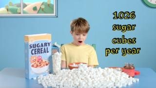 A child surrounded by sugarine cubes during breakfast and a parcel of sweetened breakfast cereal