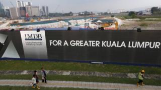 Men walk past a 1 Malaysia Development Berhad (1MDB) billboard at the funds flagship Tun Razak Exchange development in Kuala Lumpur, Malaysia, in this March 1, 2015 file photo