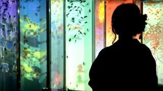 Mujer frente a un acuario