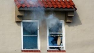 Tear gas streams from broken windows at the apartment where a suspect with a high-powered rifle was surrounded in the Bankers Hills area of San Diego (04 November 2015)