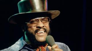 Billy Paul in glasses and a top hat, singing in to a microphone