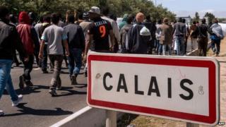 """Migrants walk past a """"Calais"""" sign"""