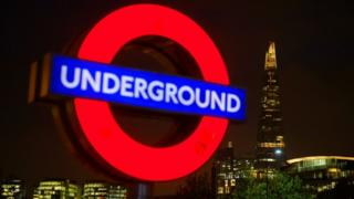 A London Underground sign is seen alongside the Shard at night