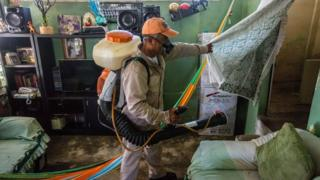 A municipality worker fumigates a home against the Aedes aegypti mosquito