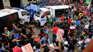 "Protesters try to trash a police mobile patrol vehicle as they join various activist and Indigenous People""s (IP) groups in a protest against the continuing presence of U.S. troops in the Philippines in front of the U.S. Embassy in metro Manila, Philippines October 19, 2016"