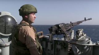 A Russian seaman stands next to a machine gun on the Russian missile cruiser Moskva (November 2015)
