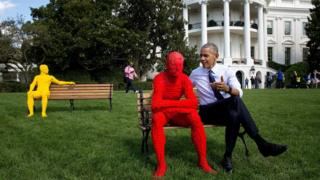 Obama sits on a bench on the White House lawn, apparently speaking to man made entirely out of red Lego bricks. The Lego man is leaning forward intently with elbows on knees.