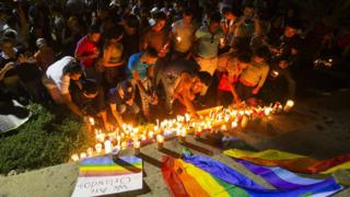 People light candles for the victims of a mass shooting at a US gay club