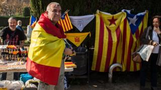 A man draped in a Spanish flag walks past a pro-independence souvenir stall outside the Catalan parliament