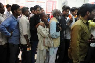 Indian people queue inside a bank to deposit 500 and 1000 Indian rupee notes in Rahimapur village on the outskirts of Allahabad on November 10, 2016.