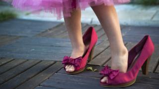 niña con zapatos y vestido rosa