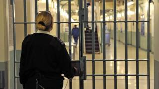 A prison officer at the doors of a prison
