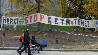 People walk past a banner hung close to the Walloon parliament in Namur on October 28, 2016