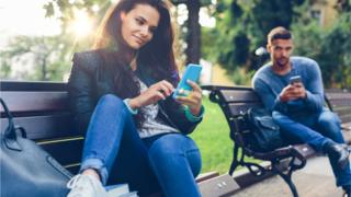 Couple on park benches on smartphones