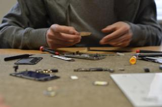 A phone which has been taken apart and is being repaired