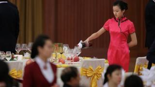 A waitress pours a bottle of wine at a banquet