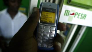 A man sending money via M-Pesa, in Nairobi