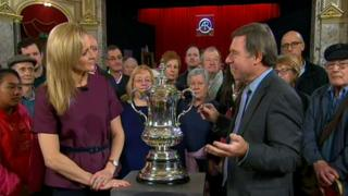 BBC Sport's Gabby Logan and Antiques Roadshow expert Alastair Dickenson with the FA Cup trophy