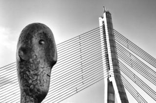 A sculpture in front of a cable bridge
