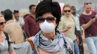 A foreigner wearing an anti-pollution mask walks a street in New Delhi, India, 5 November 2016.