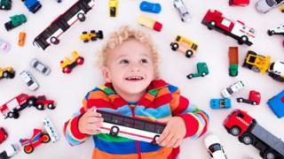 Un niño en medio de un montón de carritos y camiones de juguete