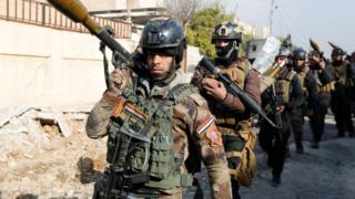 Iraqi Special Operations Forces (ISOF) carry weapons during clashes with so-called Islamic State (IS) near Mosul University, 13 January 2017